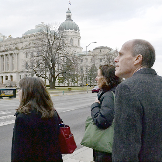 Two women and a man in coats stands at a large intersection with the Indiana State House looming in the distance.