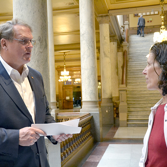A woman and male legislator stand within the ornate halls of the Indiana State House and discuss issues that affect people with developmental disabilities.
