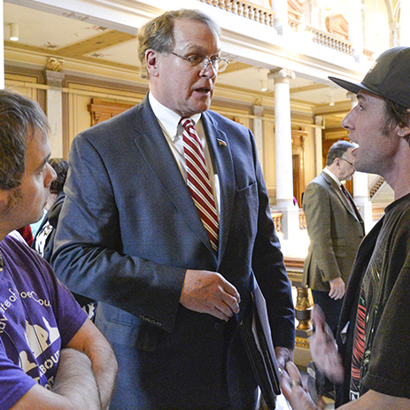 Two young men with developmental disabilities discusses issues that affect them with a male legislator in the hallways at Indiana State House.