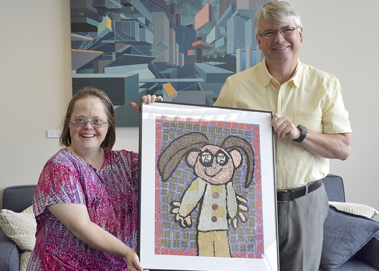 A woman with developmental disabilities presents the mayor with his portrait she created in a mixed-media mosaic fashion in his office.
