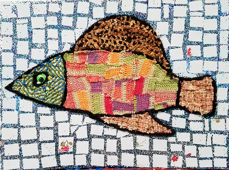 A mixed-media mosaic fish in reds, oranges, greens and browns.