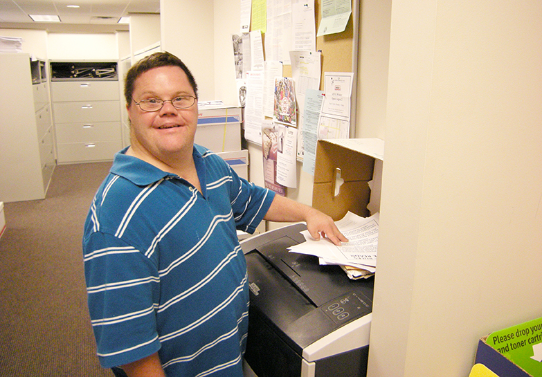 A young man with developmental disabilities, wearing a blue-and-white striped shirt and standing next to a paper shredder, smiles at the camera as he reaches for the next pieces of paper to shred.
