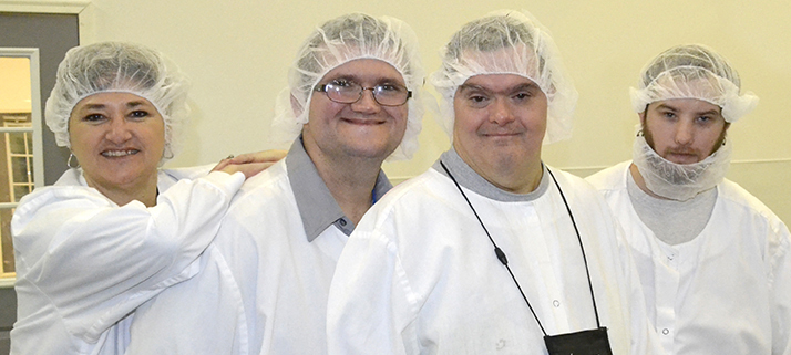 A woman staff member and three men with developmental disabilities, all in white smocks and hairnets, smile and pose for the camera.
