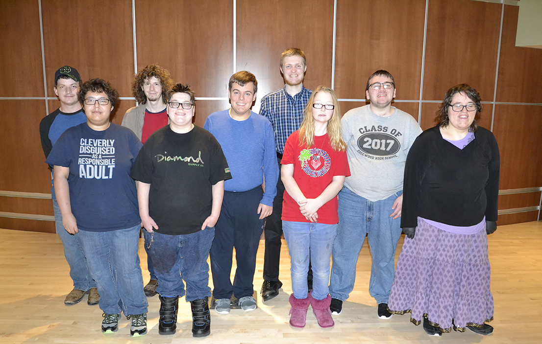 Nine young people with developmental disabilities gather in a group and smile for the camera.