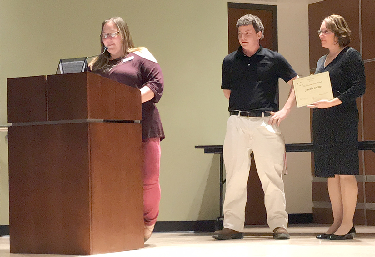 A young man stands next to a woman with a certificate, behind a woman at the podium during a presentation.