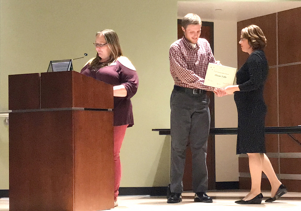 A young man accepts a certificate from a woman in a black dress as a woman in front of them stands at a podium.