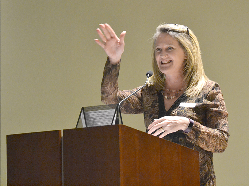 A woman smiles and gestures from the podium toward the audience, not pictured.