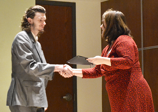 A young man in a gray suit shakes hands and accepts a certificate from a woman in a red dress.