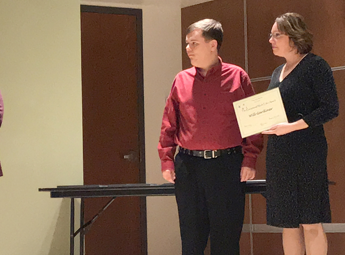 A young man in a red shirt stands next to a woman in a black dress holding a certificate, while both look toward a speaker, not pictured.