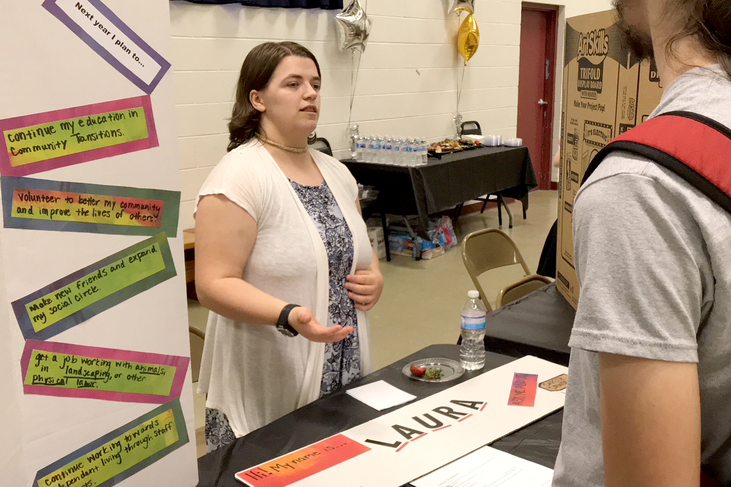 A young woman behind a table talks with a booth visitor about her experience with the Pre-Employment Transition Services program.