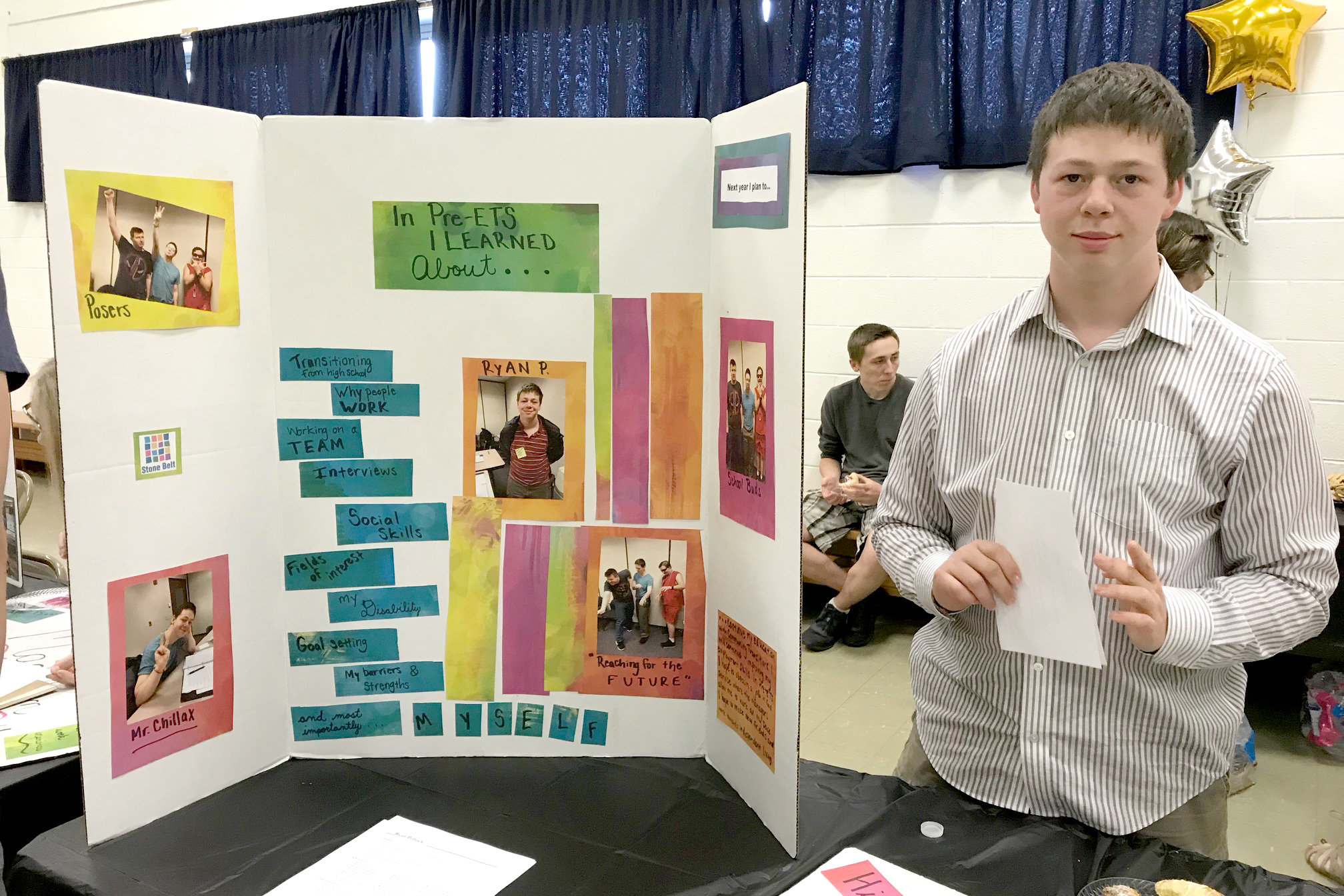A young man stands behind a table and next to his poster, waiting to talk with visitors about his experience with the Pre-Employment Transition Services program.