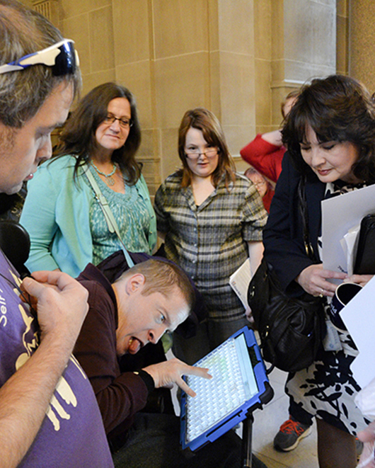 A young man using a wheelchair and communication device talks with a female legislator as his peers watch.